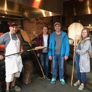 A large group of people gather in front of a pizza oven at Flatbread Pizza as seen on Off the Beaten Path Food Tours' Davis Square Food Tour.