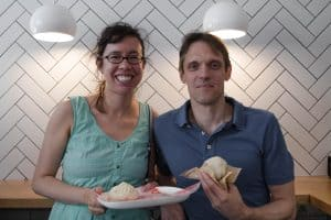 A couple smiles while standing in front of a tiled wall on an Off the Beaten Path Food Tour in Harvard Square.