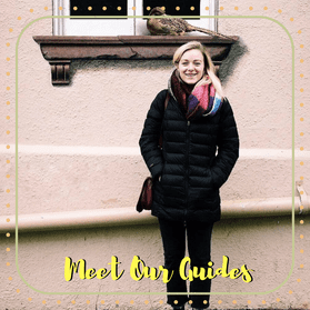Biz, an Off the Beaten Path Food Tour guide, smiles while wearing a large black coat and colorful scarf.