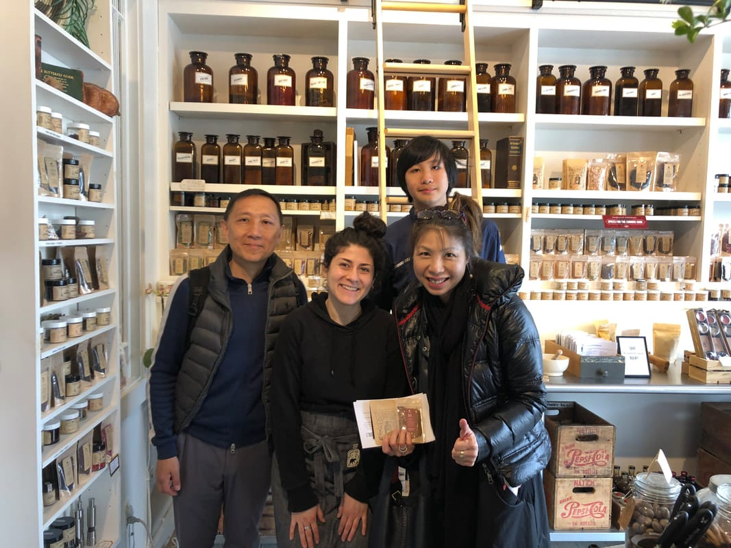 A group stands smiling in front of shelves in a shop in Davis Square, Somerville, MA.
