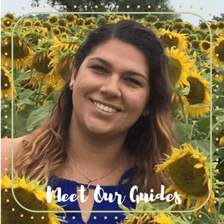 Michelle, an Off the Beaten Path Food Tour guide, stands in a field of sunflowers smiling.