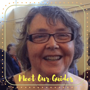 Carol, an Off the Beaten Path Food Tour guide, wears glasses and smiles at the camera.