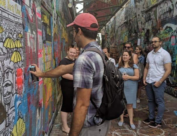 A group of people walk through Graffiti Alley in Central Square while on an Off the Beaten Path Food Tours.